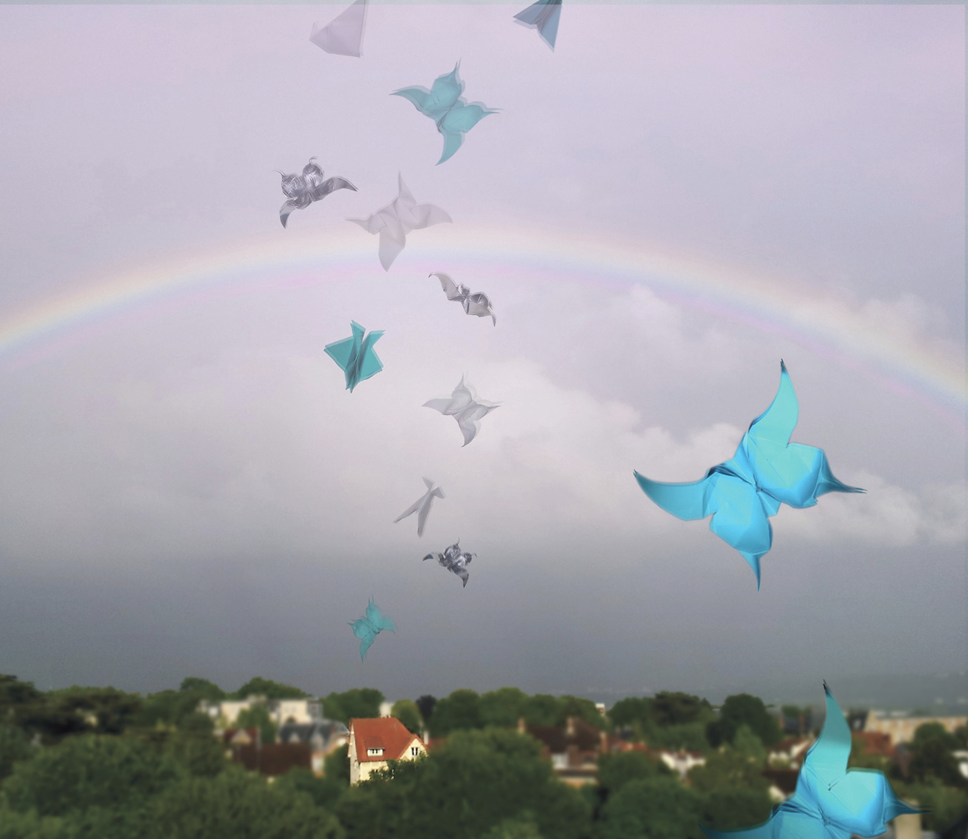 flying origami butterflies over a rainbow