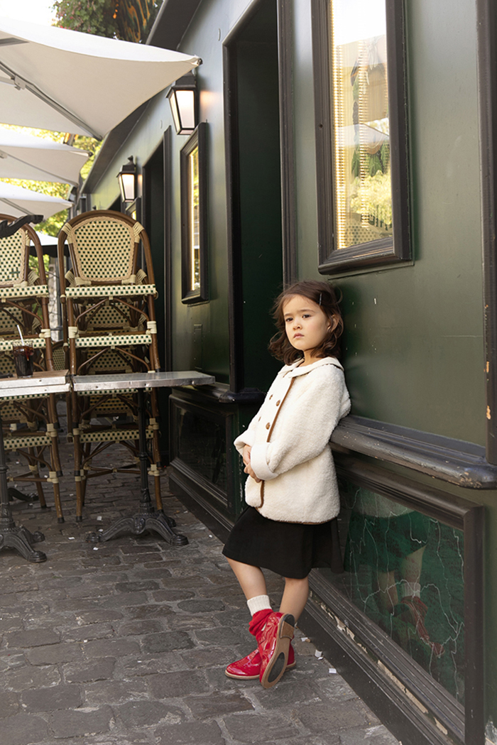 little girl thinking in front of a parisian cafe